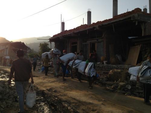 Pessoas carregam toldos de plástico para fazer abrigos